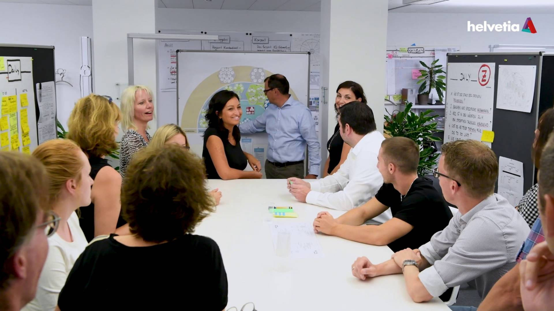 A group of people sits around a table in a daily stand-up meeting and discusses with each other.