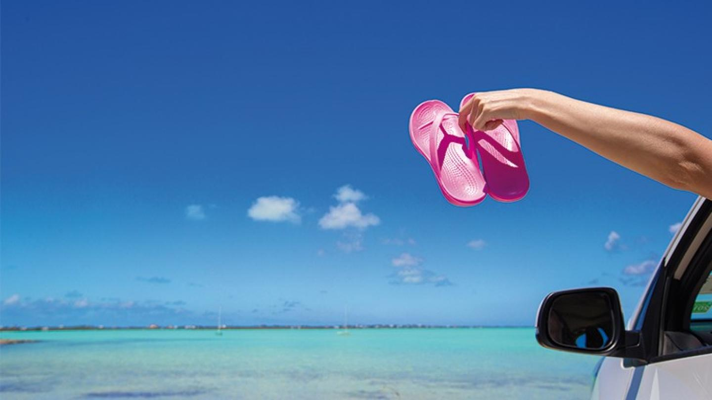Flip Flops from the window of a car on background tropical beach