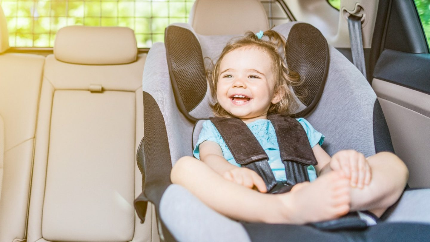 Infant baby girl buckled into her car seat.
