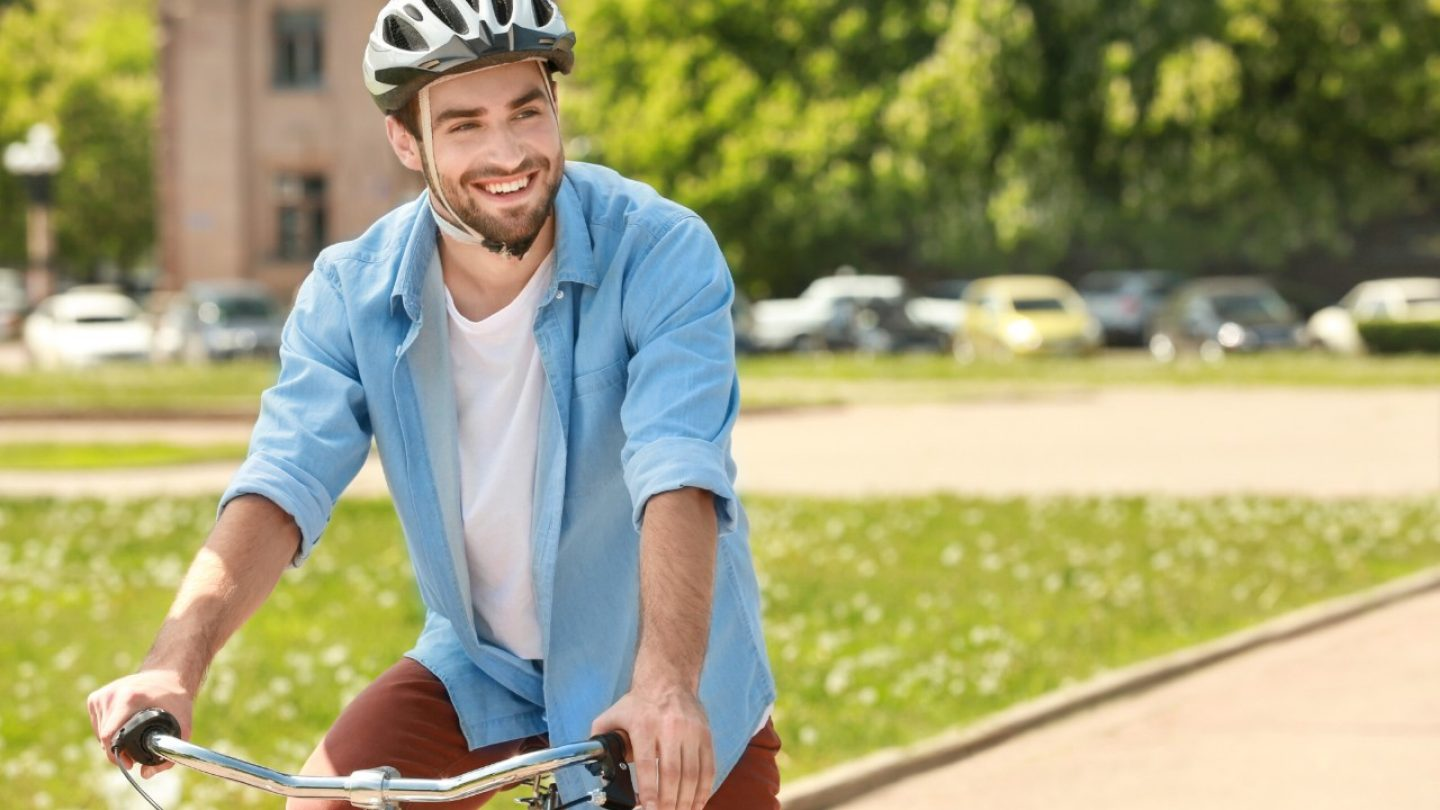 Handsome young man riding bicycle in park on sunny day