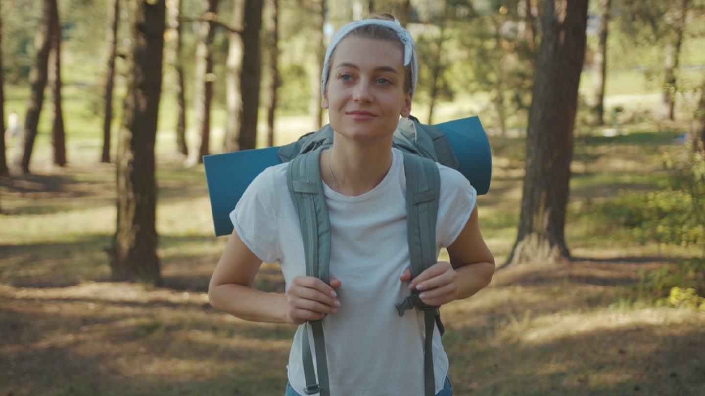 Slow motion woman young tourist with backpack walking in the fall forest on sunny summer day smile look around vacation camping hiking travel wood hike active journey young nature activity close up